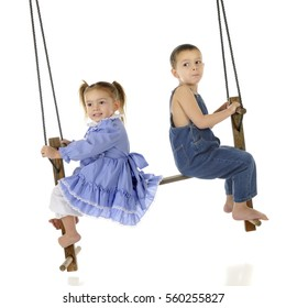 A preschool brother and sister swinging together on a rustic, antique 2-person swing.  On a white background.