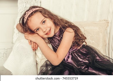 Preschool cheerful little happy girl have a good time at home near bright christmas lights and christmas tree. New year, christmas, vacations, childhood, happiness concept