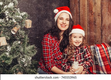 Preschool cheerful little happy girl with her mother have a good time at home near bright christmas lights and christmas tree. New year, christmas, vacations, childhood, happiness concept