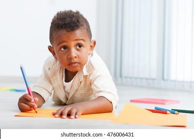 Preschool child boy drawing on the floor