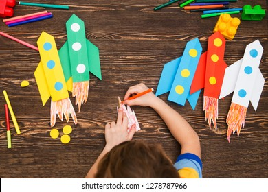 preschool Child in creativity in the home. Happy kid makes rockets from paper. Children's creativity. Creative children play with craft. Tools and materials for children's art creativity on table.
