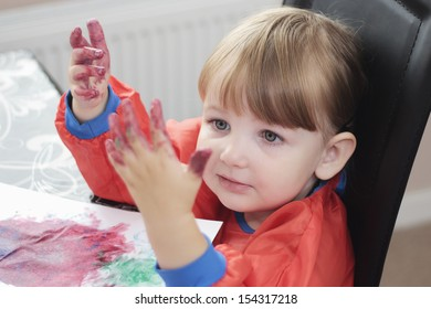preschool child looking at her paint covered hands