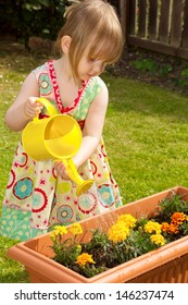 Pre-school child watering flowers in a garden with a watering can