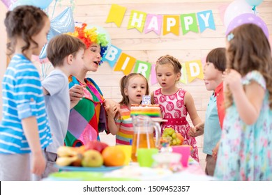 Preschool children holding by hands and blowing candle up. Little kid girl 5 years celebrating her birthday together with friends and clown