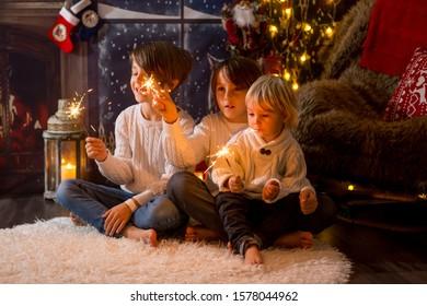 Preschool children, holding sparkler, celebrating new years eve at home