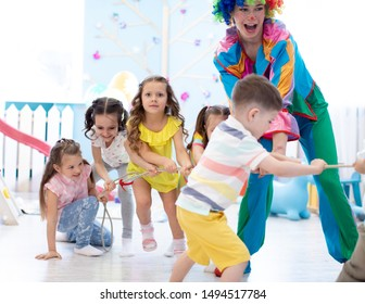 Preschool children playing teamwork game together with clown