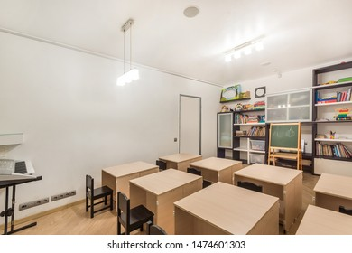 Preschool classroom interior design. Desks, chairs and blackboard. Kid room decoration and furniture with books & toys.