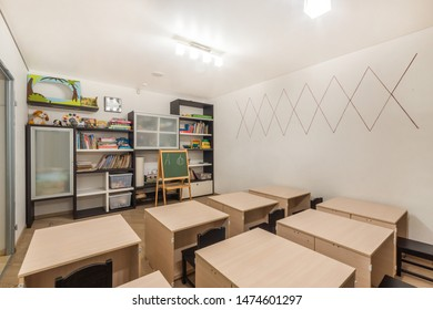 Preschool classroom interior design education. Desks, chairs and blackboard. Kid room decoration and furniture with books & toys