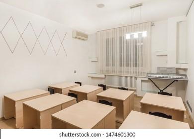 Preschool classroom interior design education. Desks, chairs and electric piano