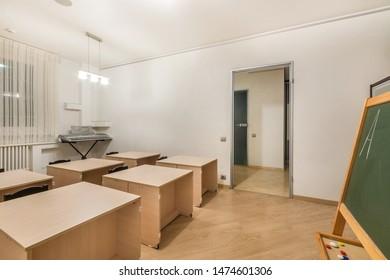 Preschool classroom interior design education. Desks, chairs, blackboard and electric piano