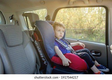 Preschool cute 3-4 years old boy sitting in safety car seat and crying during family travel by car, bad mood, negative emotion, upbringing and family concept, summer outdoor.