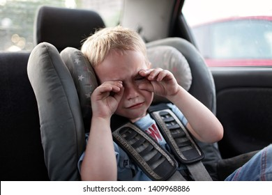 Preschool cute 4-5 years old boy sitting in safety car seat and crying during family travel by car, bad mood, negative emotion, upbringing and family concept, summer outdoor