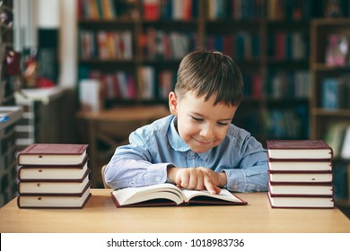 Preschool european boy is staying at the table in the library with stacks of books beside. Close-up pupil holding his hands on a book while reading. Pupil loves lecture, preparing for school.