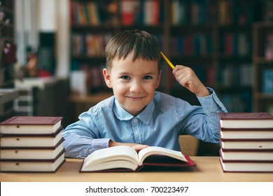 Preschool european boy is staying at the table in the library with stacks of books beside. Close-up, pupil holding his hands on a book having a plan in his mind . Boy holds yellow pencil in hair.