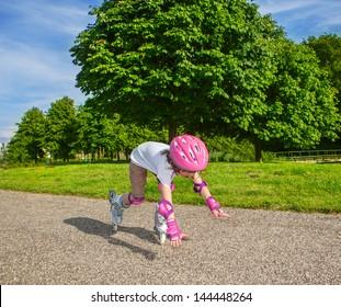 Preschool-Mädchen mit Inline-Rollschuhen auf, fallend