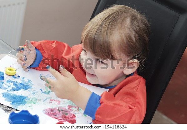 preschool girl looking at her paint covered hands and smiling