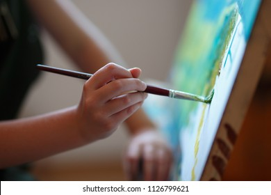 Preschool girl painting in art class. Close up photo brush in hand