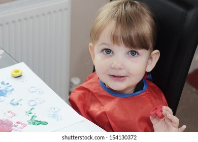 preschool girl painting a picture with foam letters, and looking directly into the camera