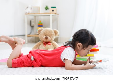Preschool girl playing indoors with tablet on carpet in big playroom at home or kindergarten