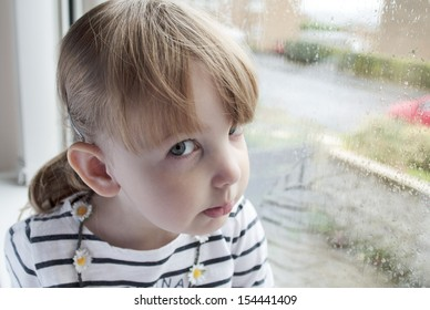 preschool girl sitting at a window on a rainy day, and looking directly at the camera