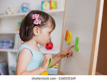 Preschool girl studying the letters of the alphabet. Child reaching up at the Board with bright letters in a white and bright room. Early development. Preparation for school.