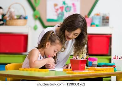 Preschool Girl and Teacher Painting in Classroom