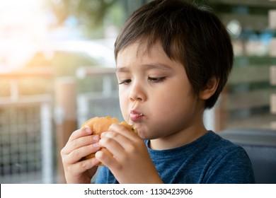 Preschool kid boy eats hamburger sitting in nursery cafe,Cute happy boy eating hamburger sitting in the restaurant,Healthy child eating delicious homemade burger,