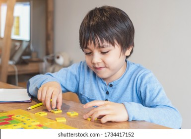 Preschool kid learning English words game,Child boy concentrated with spelling English letter with parent at home. Distance Education ,Activity for children for home schooling during self isolation