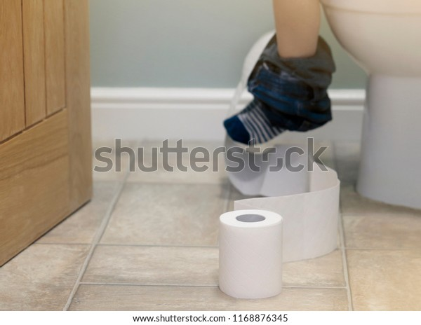 Preschool kid sitting on toilet and playing with toilet rolls,Low view of kid legs hanging with blue jeans with striped socks,Child tearing the tissue, copy space,Training child or Health care concept