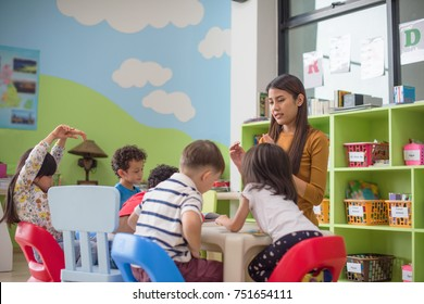 preschool kids kindergarten learning through playing in the playing room together with the teacher watching in background