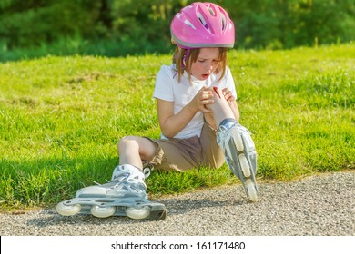 Preschool roller skate beginner looking at her bleeding knee.