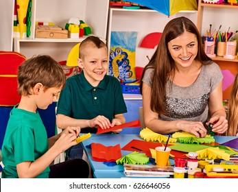 Preschool scissors in kids hands cutting paper with teacher in class room. Development and social lerning happy children in school. Children's project in kindergarten. Small group girls together.