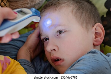 Pre-school sick boy lying on pillow in bed with illness. Mother is measuring body temperature on his forehead with modern digital thermometer. - Image