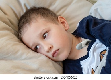 Pre-school sick boy in pyjama lying on pillow in bed with a digital thermometer. Ill boy is measuring body temperature and doesn't feel well. - Image