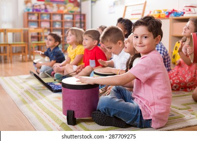 Étudiants de maternelle jouant d'instruments de musique.