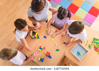 Preschool teacher with children playing with colorful wooden didactic toys at kindergarten. View from above.