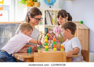 Preschool teacher with children playing with colorful wooden didactic toys at kindergarten