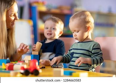 Preschool teacher and cute children boys having fun time playing