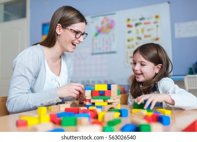 Preschool Teacher and Cute Girl Having Fun Time Playing