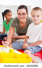 preschool teacher and kids in classroom