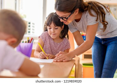 Preschool teacher looking at smart child learning to write and draw. Early education. Harnessing creativity and support.