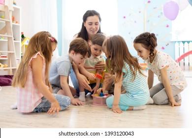 Preschool teacher plays with group of children sitting on a floor at kindergarten