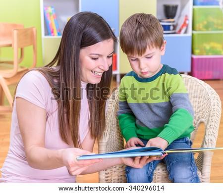 Preschool Teacher Reading A Book To Boy At Kindergarten