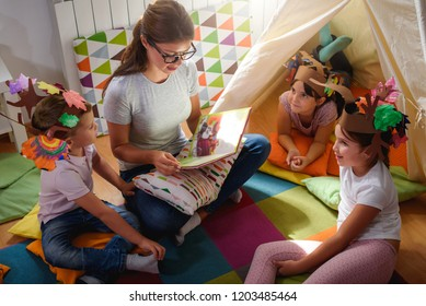 Preschool teacher reading a story to children at kindergarten. Mother reading to the children.