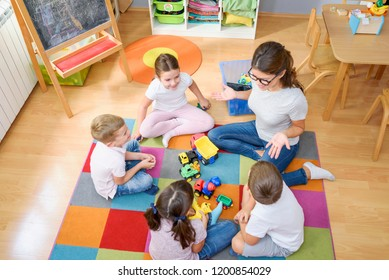 Preschool teacher talking to group of children sitting on a floor at kindergarten