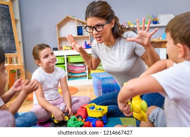 Preschool teacher talking to group of children sitting on a floor at kindergarten