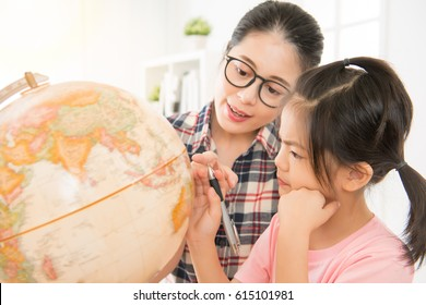 preschool teacher teaching cute girl kid about globe in geography class at school. young kid holding pen and focus on the map thinking.