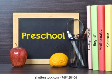 Preschool text on blackboard and preschool text books (Reading/Phonics, English, Mathematics, science). A preschool is an educational stage for early childhood education before primary school.