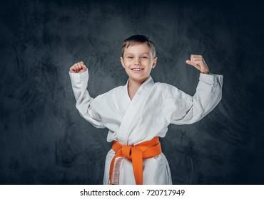 Preschooler boy dressed in a white karate kimono with orange belt.