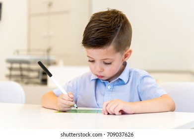 preschooler child boy learn to write letter in the classroom